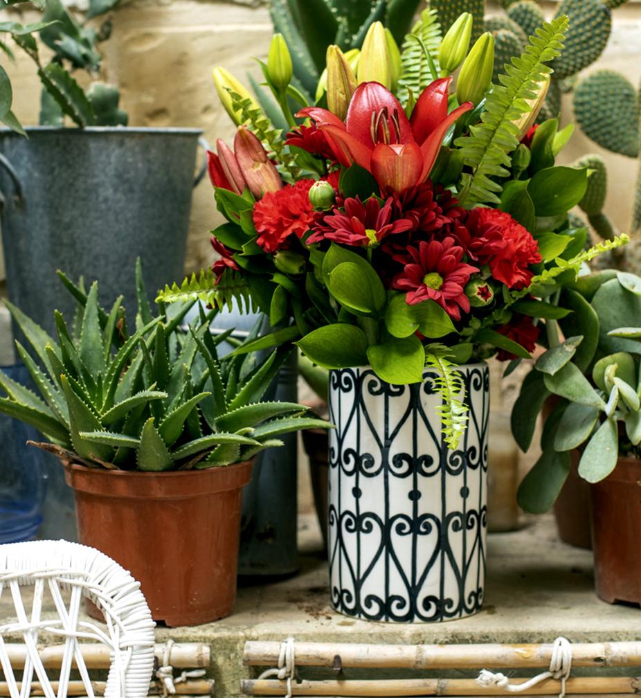 Vase Qalbiena red flowers in yard